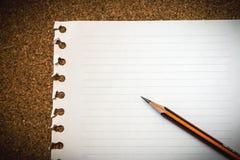 Papper och blyertspenna på korkbrädet Royaltyfri Fotografi
