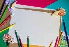 Papper och färgade blyertspennor arkivbilder