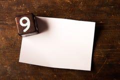 Papper och träkub med nummer på trätabell, 9 royaltyfri bild