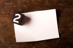 Papper och träkub med nummer på trätabell, 2 royaltyfria foton
