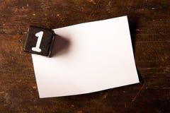 Papper och träkub med nummer på trätabell, 1 royaltyfri fotografi