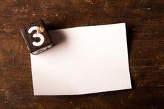 Papper och träkub med nummer på trätabell, 3 royaltyfria bilder