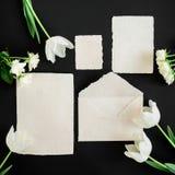 Papper packar in, vita kort och blommor på svart bakgrund Lekmanna- lägenhet, bästa sikt Idérikt valentindagbegrepp Arkivbilder