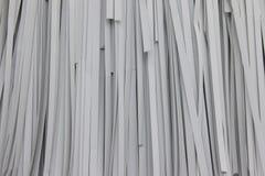 Papper som strimlas på vit bakgrund Hängning för pappers- dokumentförstörare på den vita väggen Royaltyfria Bilder