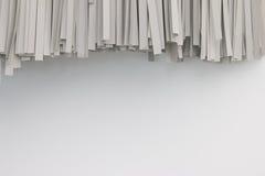 Papper som strimlas på vit bakgrund Hängning för pappers- dokumentförstörare på den vita väggen Fotografering för Bildbyråer