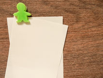 Pappers- anmärkning med det gröna gemet på wood bakgrund Arkivfoton