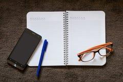 Pappers- anmärkning med mobilen, pennan och glasögon på mattan Arkivbilder