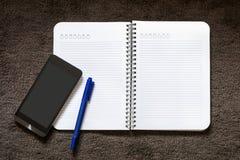 Pappers- anmärkning med pennan och mobil på mattan Fotografering för Bildbyråer