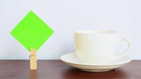 Pappers- anmärkning och kopp på trätabellen arkivbilder