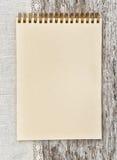 Pappers- anteckningsbok- och linnetyg på det gamla trät Royaltyfri Foto
