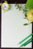 Pappers- ark, klocka, blyertspennor, mintkaramell och äpple på mörk träbackgound Royaltyfri Bild