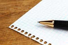 Pappers- ark med pennan på ett träskrivbord royaltyfri bild