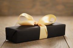 Pappers- ask för handgjord gåvasvart med den gula bandpilbågen på den wood tabellen Arkivbild