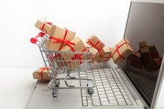 Pappers- askar i en shoppingvagn på ett bärbar datortangentbord Idéer om e-kommers, en transaktion av köpande eller säljagods ell Arkivfoton