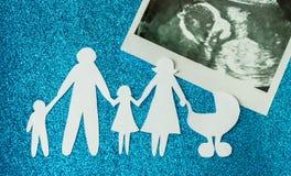 Pappers- bild av lyckliga familjer som förväntar ett annat barn arkivbilder