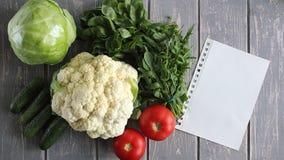 Pappers- blad och sammansättning av grönsaker på det gråa träskrivbordet Royaltyfri Bild