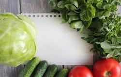 Pappers- blad och sammansättning av grönsaker på det gråa träskrivbordet Arkivbilder