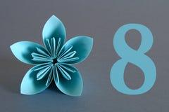 Pappers- blomma från origami med numret åtta på en grå bakgrund Mars 8, internationella kvinnors dag Arkivbilder