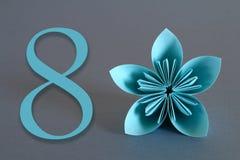 Pappers- blomma från origami med numret åtta på en grå bakgrund Marschera 8, internationell dag för kvinna` s arkivbild