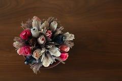 Pappers- blommor i krukan på trätabellen arkivfoto