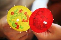 Pappers- dekorativa paraplyer i händer royaltyfria bilder