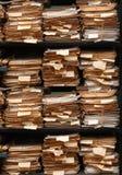 Pappers- dokument som staplas i arkiv Arkivfoto