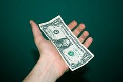 Pappers- dollar på en gömma i handflatan royaltyfri foto