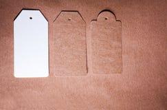 Pappers- etikett tre av olik form på hantverkpappersbakgrund Arkivfoto