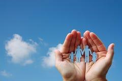 Pappers- familj i händer på för bakgrundsvälfärd för blå himmel begrepp royaltyfri bild
