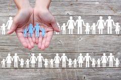 Pappers- familj i händer på träbakgrund med vita familjer royaltyfri fotografi