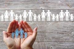 Pappers- familj i händer på träbakgrund med vita familjer arkivbilder