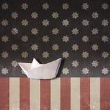 Pappers- fartyg på USA-flagga Royaltyfri Foto