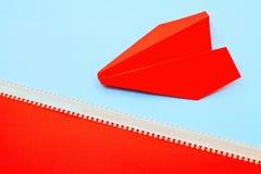 Pappers- flygplan med pillinjen på rosa färg- och blåttbakgrund royaltyfria foton