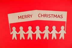 Pappers- folk som rymmer ett tecken Julfilial och klockor royaltyfri foto