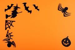 Pappers- halloween garnering på den orange bakgrunden arkivbilder