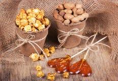 Pappers- hink av karamellpopcorn, grillade jordnötter i skal och klubbor Ställ in mål för en film Arkivbild