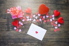 Pappers- hjärta- och gåvaask på det träröda kortet för inbjudan för bokstav för hjärtavalentindag för vän royaltyfri bild