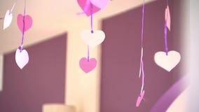 Pappers- hjärtor dinglar på band, valentins dag, inomhus