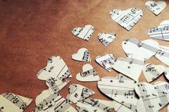 Pappers- hjärtor med musikanmärkningar Arkivfoto