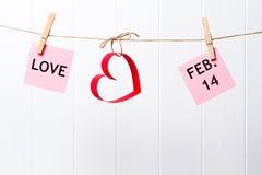 Pappers- hjärtor och FÖRÄLSKELSE och FEBRUARI 14 som hänger på linjen på vit bakgrund Royaltyfri Fotografi