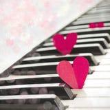 Pappers- hjärtor på piano Arkivfoto
