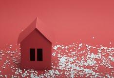 Pappers- hus i snö på röd bakgrund Fotografering för Bildbyråer