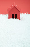 Pappers- hus i snö på röd bakgrund Arkivbilder