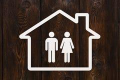 Pappers- hus med mannen och kvinnan inom Hus familjbegrepp Arkivfoto