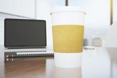 Pappers- kaffekopp med bärbara datorn och penna på den bruna tabellen Royaltyfri Foto