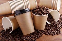 Pappers- kaffekoppar med bönor Fotografering för Bildbyråer