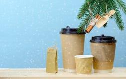 Pappers- kaffekoppar på en trätabell med granträdet royaltyfria bilder