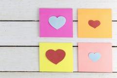 Pappers- klibbiga anmärkningar med hjärta formade pappers- snittouts på trä Royaltyfri Foto