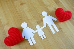 Pappers- kontur av familjen med röd hjärta på trä Royaltyfria Bilder