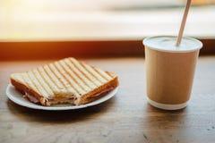 Pappers- kopp kaffe och biten smörgås på träbakgrund arkivfoto